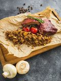 Barbecued spare ribs, buckwheat with mushroom and tomatoes on wooden cutting board. Royalty Free Stock Images