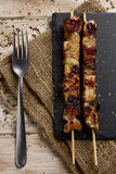 Barbecued spiced chicken meat skewers. High-angle shot of some barbecued spiced chicken meat skewers on a slate tray, placed on a rustic wooden table stock image