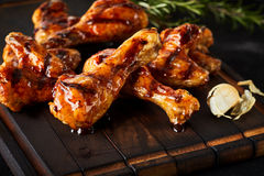 Barbecued spicy chicken wings and legs. With crispy browned skin served on a wood board as a tasty appetizer or snack stock image