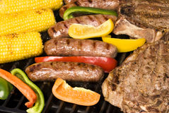 Barbecued steak, bratwurst and corn on the cob Stock Photo