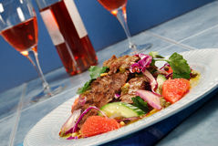 Barbecued steak salad and wine. Barbecued beef steak salad with dressing and glasses of wine royalty free stock photography