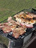 Barbecued steak and sausages on the grill Stock Photography