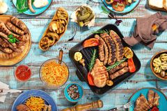 Barbecued steak, sausages and grilled vegetables on wooden picni. Appetizing barbecued steak, sausages and grilled vegetables on wooden blue picnic table, top Stock Photo