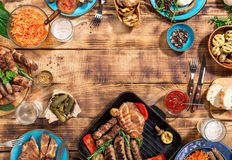 Barbecued steak, sausages and grilled vegetables on wooden picni. Appetizing barbecued steak, sausages and grilled vegetables on a wooden picnic table with copy Royalty Free Stock Photo