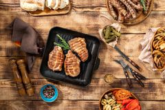 Barbecued steak, sausages and grilled vegetables on wooden picni. Appetizing barbecued steak, sausages and grilled vegetables on wooden picnic table, top view Stock Photo
