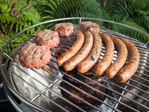 Barbecueing sausages and beefburgers Royalty Free Stock Images