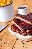 Barbecueribben op houten lijst met gebraden gerechten Stock Foto