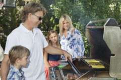 Barbecuing семьи из четырех человек Стоковое Изображение RF