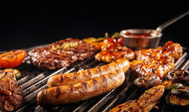 Barbecuing an assortment of meat. With pork sausages, beef steak, chicken wings onions, tomatoes and slice garlic bulbs in a low angle close up view stock photo