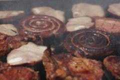 Barbecuing meat on charcoal fire closeup image. Stock Photos