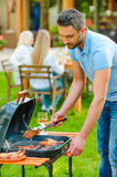 Barbecuing meat to perfection. Stock Photo