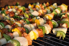 Barbecuing skewers Stock Images