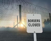 Barbed and razor wire on a fence with a sign `borders closed