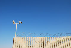 Barbed security. Fence with tracking cameras and barbed wire and on blue sky background Stock Photography