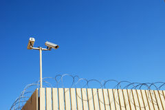 Barbed security. Fence with tracking cameras and barbed wire and on blue sky background Stock Photos