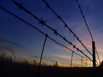 Barbed Sunrise. Barbed Fence Silhouette Royalty Free Stock Photo