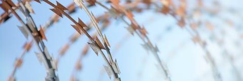 Barbed taśma krajacz przeciw niebieskiemu niebu jako strona internetowa chodnikowiec Fotografia Stock