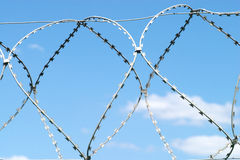 Barbed twisted wire on sky with clouds Royalty Free Stock Photos