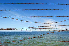 Barbed Wire. Wire entanglement on the background of sky and sea Royalty Free Stock Photography