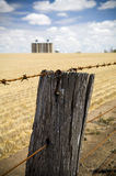 Barbed Wire. Rusty barbed wire fence with harvested wheat field and grain silo's in background stock photos
