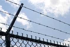 Barbed wire. On top of chain security fence against blue cloudy sky Stock Image