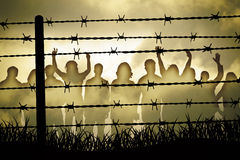 Barbed wire. People are captured behind barbed wire Stock Photo