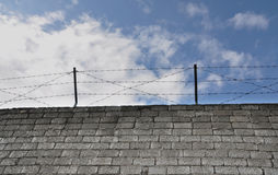 Barbed wire above a stone wall. The barbed wire hangs above a stone wall Royalty Free Stock Image