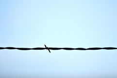Barbed Wire Against Blue Sky. A strand of western barbed wire against a blue sky stock photo
