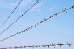Barbed wire against blue sky Stock Images