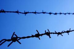 Barbed wire against blue sky, selective focus Stock Photo