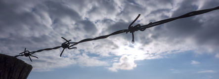 Barbed wire against clouds sky Stock Photography