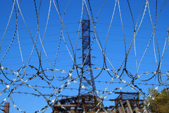 Barbed wire against a mast of power lines Stock Photos