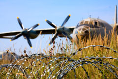 Barbed wire and the aircraft Stock Photos