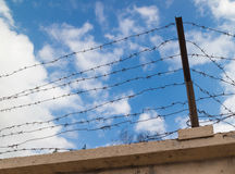 Barbed wire around the prison. On the background of blue sky royalty free stock image