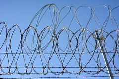 Barbed wire atop the border wall separating the USA and Mexico. Barbed wire and Concertina wire atop the border wall separating the United States and Mexico royalty free stock photo