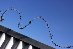 Barbed wire atop of corrugated iron against a blue Stock Photos