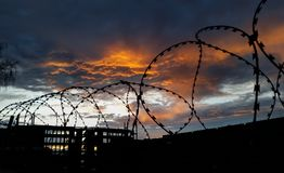 Barbed wire on a background of clouds and crimson sunset. Black silhouette of barbed wire fence enclosing the prison and protected zone polygon with unfinished Royalty Free Stock Photography