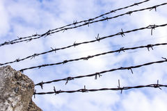 Barbed wire on a background of white-blue sky. Barbed wire, also known as barb wire, less often bob wire or, in the southeastern United States, bobbed wire, is a Royalty Free Stock Images