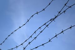 Barbed wire. Barbed wire on fence with blue sky to feel worrying stock photography