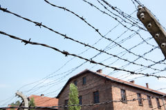 Barbed wire and barracks in Auschwitz camp. Barbed wire fence and group of prisoner barracks in the background. Auschwitz concentration camp Stock Image