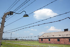 Barbed wire and barracks in Auschwitz camp. Barbed wire fence and a prisoner barrack in the background. Auschwitz concentration camp Stock Photography