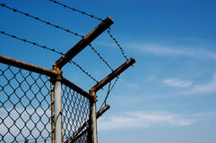 Barbed wire with blue sky. Chain link fence with barbed wire Stock Photography