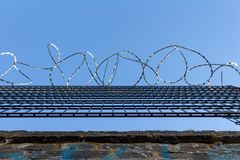 Barbed wire on blue sky background - Lost freedom and hope concept stock photography