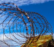 Prison. Barbed wire. Barbed wire on blue sky background with white clouds. Wire boom. Military conflict . Syria. Barbed wire. Barbed wire on blue sky background Royalty Free Stock Image