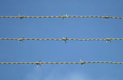 Barbed wire on blue sky metal fence security barrier Stock Image