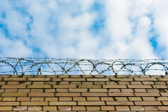 Barbed wire on a brick wall against a blue sky with clouds. Royalty Free Stock Photo