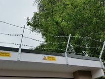 Barbed Wire on Building Roof. Barbed wire construction on the roof of a modern building. Photographed with a tree in the background and danger signs stock images