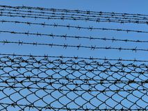The barbed wire cage captures the background of the blue sky. Barbed wire cage prevents entry royalty free stock photos