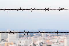 Barbed wire and city view. Background Stock Photography