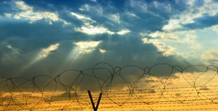 Barbed wire and cloudy sky Stock Photos